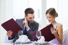 Smiling couple with menus at restaurant. Restaurant, couple and holiday concept - smiling men looking into girlfriends or wifes menu at restaurant Stock Photo