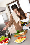 Smiling couple in modern kitchen cook together Stock Images