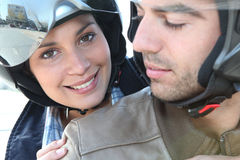 Smiling couple on a motorbike royalty free stock images