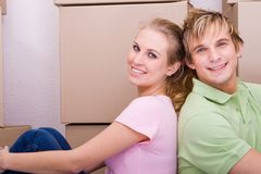Smiling couple moving. Smiling blonde couple sitting back to back Royalty Free Stock Photography