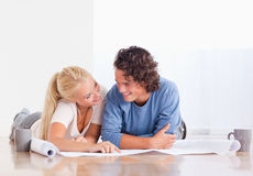 Smiling couple moving in a new house. Looking at a plan royalty free stock photo