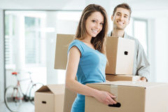 Smiling couple moving in a new house. Happy smiling couple moving in a new house and carrying carton boxes, relocation and renovation concept stock photo