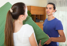 Smiling couple moving sofa together Stock Image