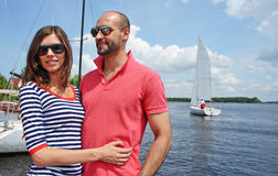 Smiling couple near water in port. The perfect smiling couple near water in port. The yacht on background Stock Image