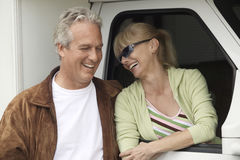 Smiling Couple Next To RV. Smiling mature couple next to RV royalty free stock images