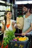 Smiling couple with notepad shopping for vegetables in organic section Royalty Free Stock Photos