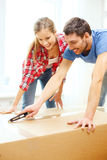 Smiling couple opening big cardboard box Royalty Free Stock Images
