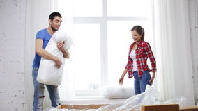 Smiling couple opening big cardboard box with sofa Royalty Free Stock Photography