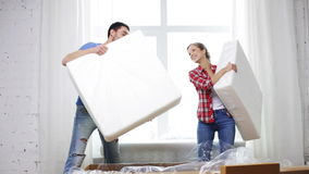 Smiling couple opening big cardboard box with sofa. Repair, building and home concept - smiling couple opening big cardboard box with sofa stock video