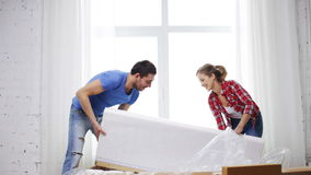 Smiling couple opening big cardboard box with sofa. Repair, building and home concept - smiling couple opening big cardboard box with sofa stock footage