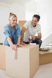 Smiling couple packing boxes in a new house Royalty Free Stock Photography