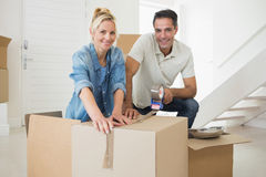 Smiling couple packing boxes in a new house Stock Photos