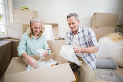 Smiling couple packing mug in a box Royalty Free Stock Photography