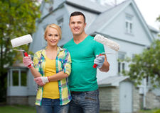 Smiling couple with paint rollers over house Royalty Free Stock Photography