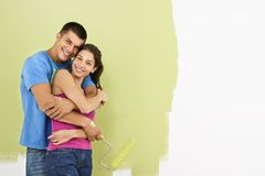 Smiling couple painting. Attractive smiling couple posing in front of partially painted wall holding paint roller royalty free stock photos