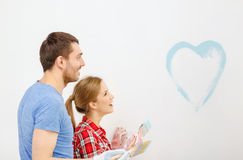 Smiling couple painting small heart on wall Stock Photo