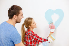 Smiling couple painting small heart on wall Royalty Free Stock Photography