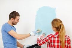 Smiling couple painting wall at home. Repair, building and home concept - smiling couple painting wall at home royalty free stock photos