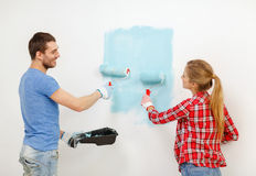 Smiling couple painting wall at home. Repair, building and home concept - smiling couple painting wall at home royalty free stock photography