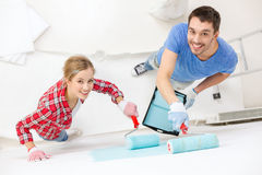 Smiling couple painting wall at home. Repair, building and home concept - smiling couple painting wall at home royalty free stock image