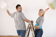 Smiling couple painting wall together Royalty Free Stock Photo