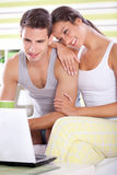 Smiling couple in pajamas with laptop Royalty Free Stock Photography