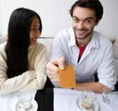 Smiling couple paying for meal at restaurant Stock Images