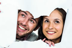 Smiling couple peeking out torn paper Royalty Free Stock Photography