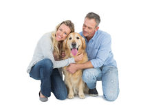 Smiling couple petting their golden retriever Royalty Free Stock Photography