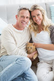 Smiling couple petting their gringer cat on rug Royalty Free Stock Images