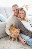 Smiling couple petting their gringer cat on rug Royalty Free Stock Photo