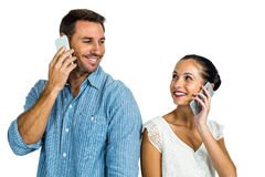 Smiling couple on phone call looking at each other. On white screen Stock Photo