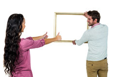 Smiling couple with picture frame Royalty Free Stock Photo