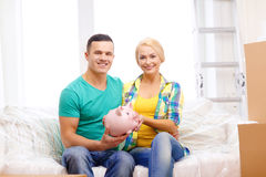 Smiling couple with piggybank in new home. Moving, home and couple concept - smiling couple with piggybank in new home royalty free stock photography