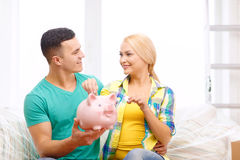 Smiling couple with piggybank in new home Stock Photos
