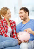 Smiling couple with piggybank sitting on sofa Royalty Free Stock Photos