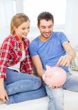 Smiling couple with piggybank sitting on sofa Stock Image