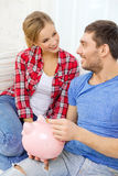 Smiling couple with piggybank sitting on sofa Royalty Free Stock Images
