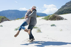 Smiling couple playing on the beach in warm clothing Royalty Free Stock Photography