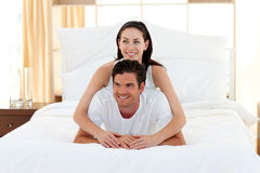 Smiling couple playing on bed together Royalty Free Stock Images