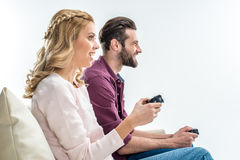 Smiling couple playing with joysticks Stock Images