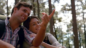 Smiling couple pointing away on a hike stock footage