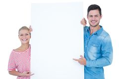 Smiling couple pointing at blank sign in their hands. On white background Royalty Free Stock Image