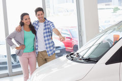 Smiling couple pointing a car Stock Images