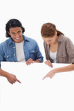 Smiling couple pointing down on blank wall Royalty Free Stock Image