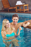 Smiling couple in pool holding Royalty Free Stock Photos