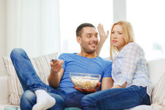 Smiling couple with popcorn choosing what to watch Royalty Free Stock Photography