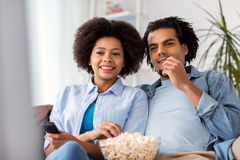 Smiling couple with popcorn watching tv at home Royalty Free Stock Images