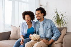 Smiling couple with popcorn watching tv at home Stock Photo