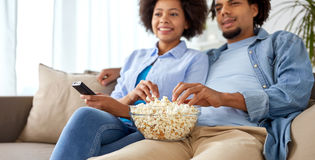 Smiling couple with popcorn watching tv at home Royalty Free Stock Photo